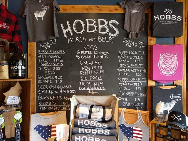 A list of to-go items from the Hobbs Tavern - including shirts, growlers, six packs, kegs, and koozies